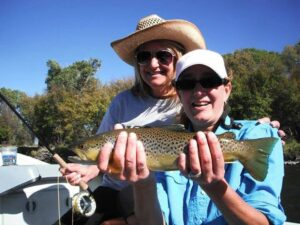 Krista Rock showing her sister how to haul in mega Browns on the Madison in MT