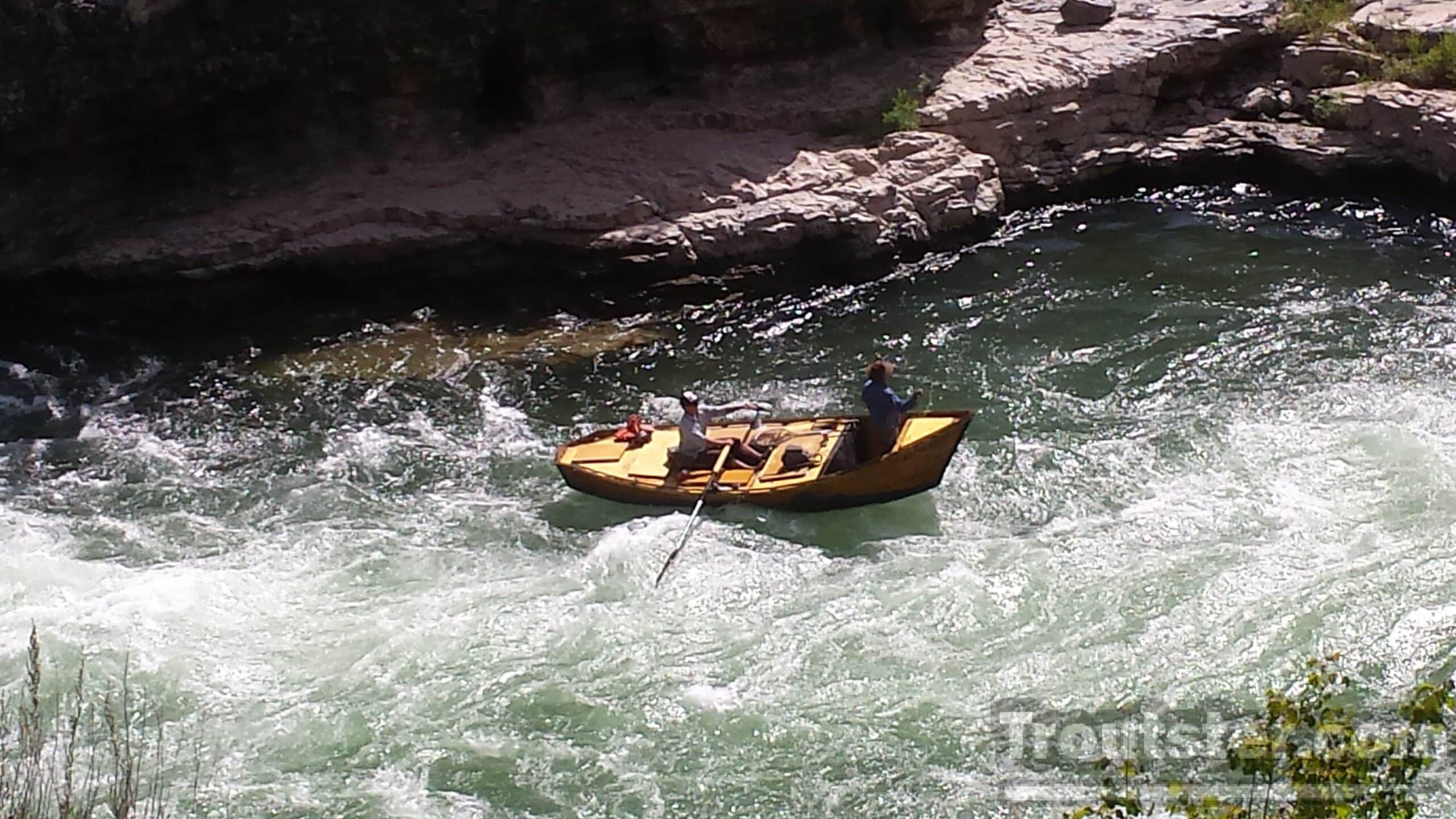 A wooden drift boat running through rapids